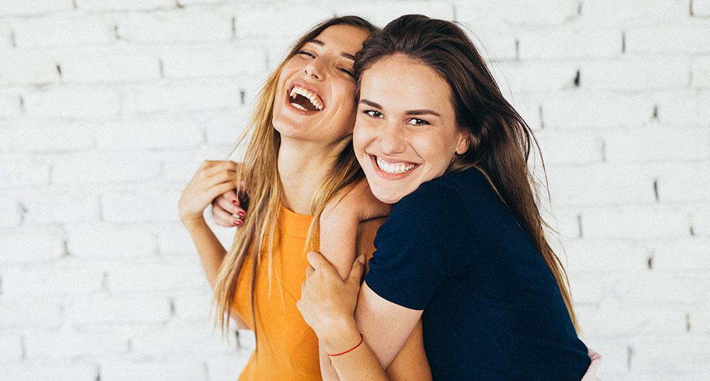 Zwei Frauen, die sich umarmen und zusammen lachen