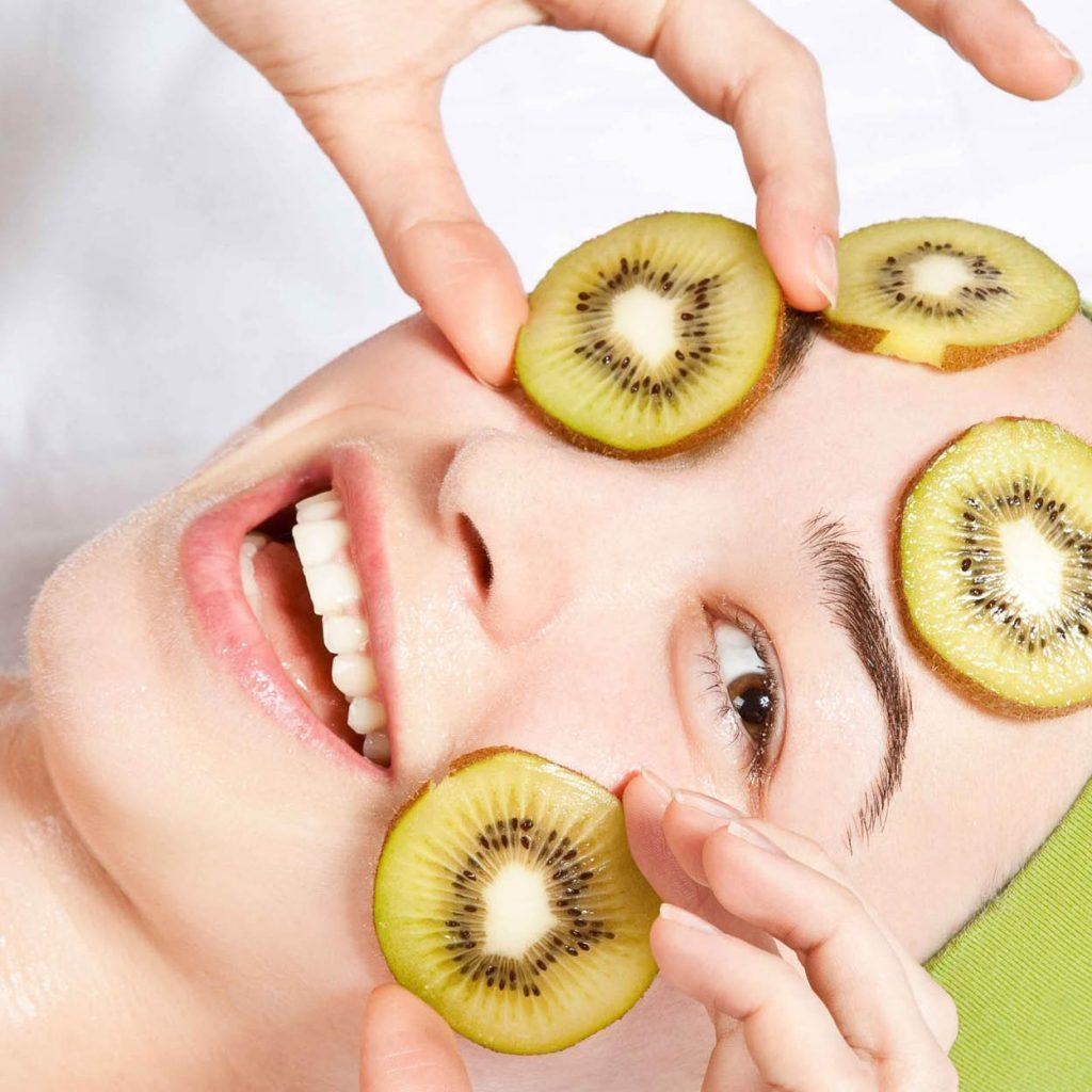 Frau mit Kiwi Scheiben im Gesicht