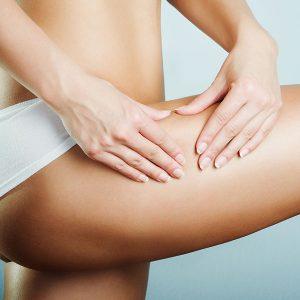 Junge Frau mit straffer Haut greift mit zwei Händen an ihr Bein