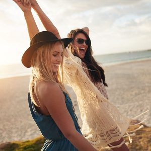 Zwei junge Frauen strecken lachend ihre Arme in die Höhe