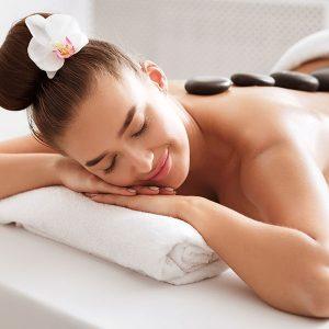 Glückliche junge Frau mit Blumen im Haar bei einer Hot Stone Massage