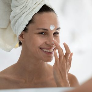 Junge Frau mit Creme im Gesicht