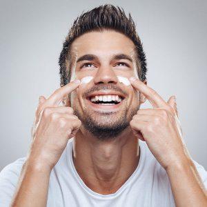 Mann mit Bart und lächelndem Gesicht. Er cremt sich gerade ein.