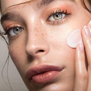 Modern und bunt geschminkte junge Frau mit Sommersprossen stricht sich wenig Creme ins Gesicht