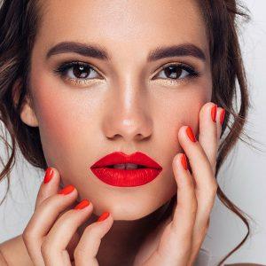 Beauty Shot von einer Frau mit geschminkten Lippen und Fingernägeln