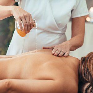 Massage-Öl wird auf den Rücken einer jungen Frau geträufelt