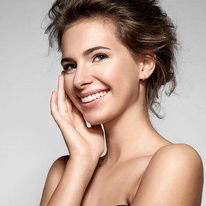 Lächelnde junge Frau mit einer Hand im Gesicht