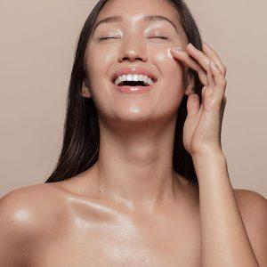 Glückliche, glänzende asiatische junge Frau mit Creme im Gesicht
