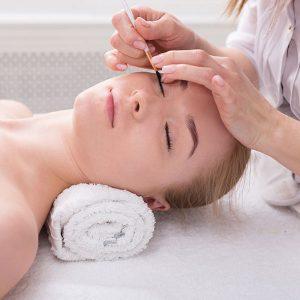 Kosmetische Wimpernbehandlung einer Frau von einer professionellen Kosmetikerin